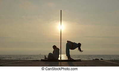 Pole dance fitness exercise on the beach. Pole dancers...