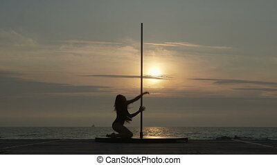 Pole dance fitness exercise on the beach at sunset....
