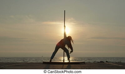 Young woman pole dancer stretching before outdoor poledance...
