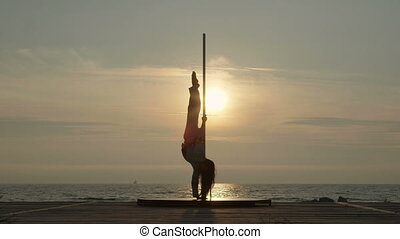 Young woman pole dancer stretching before outdoor poledance workout by the sea