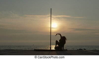 Pole dance fitness exercise on the beach. Silhouette of...