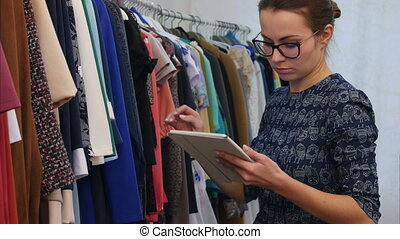 Portrait of attractive clothing store owner woman holding digital tablet in her hands and working in store