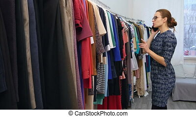 Cute young woman talking on her cell phone while checking out some clothes at the store