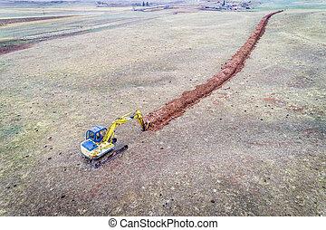 backhoe excavator digging a ditch - backhoe excavator...