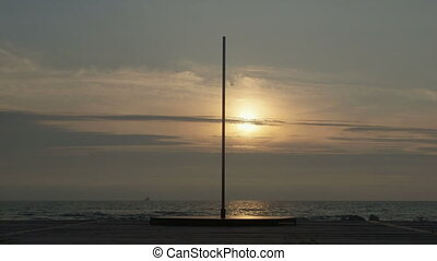 Empty portable dance pole on the beach at sunset