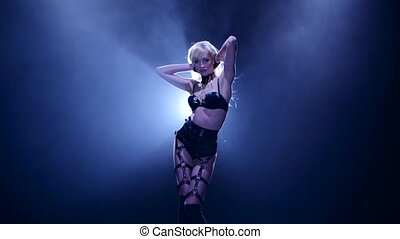 Woman pj is dancing in sexy leather lingerie. Smoky studio -...