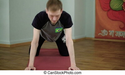 A man yoga makes a healthy stretching in the studio - A man...