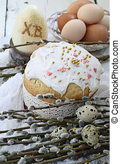 Easter cake with colored eggs and willow twigs on a wooden...