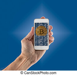 Bitcoins emerging from app on handheld smartphone - Gold...