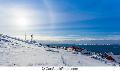 Arctic Sun Halo shining over houses at the fjord of Nuuk...