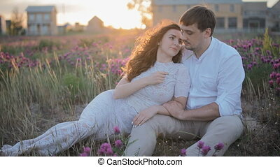 Young caucasian couple sit in the field with violet...