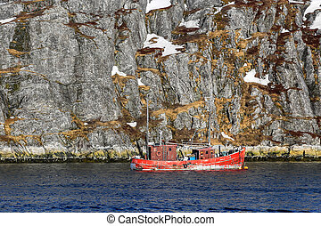 Lone fishing boat floating near steep cliff, Nuuk fjord,...