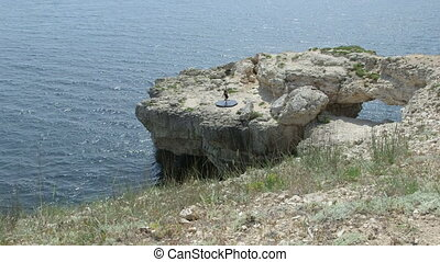 Young woman pole dancer performing pole dance on rocky cliff by sea
