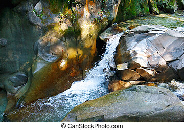 Small fair waterfall among the rocks in mountain forest -...