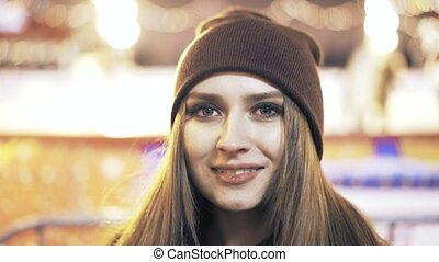 Close up of a woman in a beanie looking at camera
