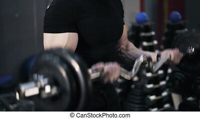 Close up of a man in black doing a barbell exercise