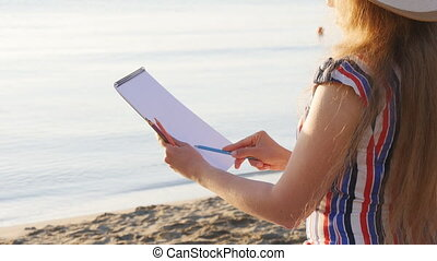 Young woman is painting on the beach. Artist