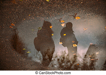 Rainy walk in the fall of two people. Reflection in a puddle...