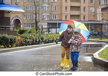 Two little boys, squat on a puddle, with little umbrellas....