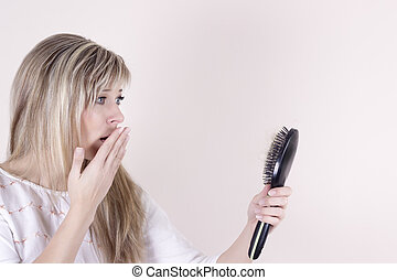 Hair loss. Depressed young woman looking at her hairbrush...