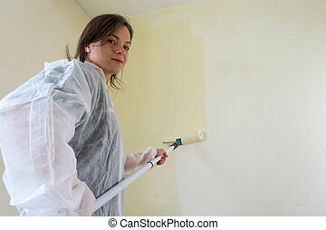 Young female student painting her room. Millenial...