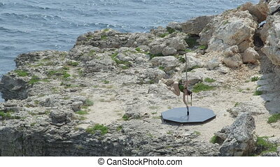 Outdoor pole dance fitness exercise above the sea.