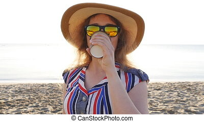 Young woman drinking coffee on the beach. Travel concept