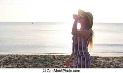 Young woman drinking coffee on the beach