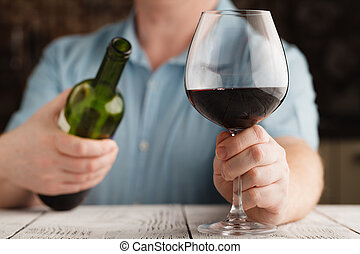man holding a glass with red wine and bottle