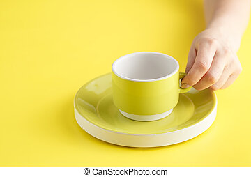 Empty yellow coffee or tea cup on yellow background.