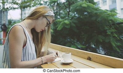 Slow motion of young beautiful blonde woman dreaming and writing in her journal, diary. Female write in notebook and drinking coffee in terrace of cafe.
