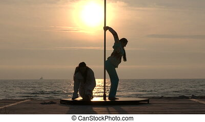 Pole dance fitness exercise on the beach. Young women...