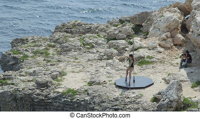 Photographer taking pictures of pole dancer during pole dance above the sea