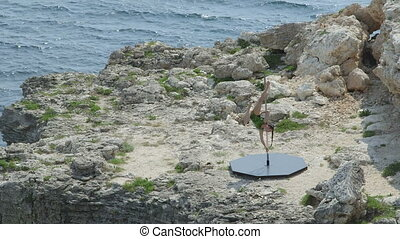 Outdoor pole dance fitness exercise above the sea. Fit girl...