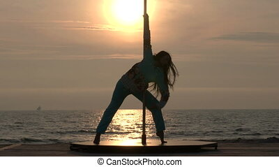 Pole dance fitness exercise on the beach
