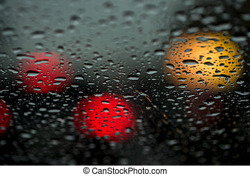 View of the modern city through the window on a very dark stormy night. Concept life of a modern city, urban traffic, night car driving. Abstract background.