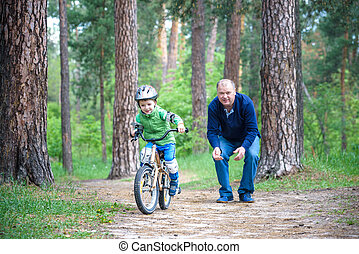 Little kid boy of 3 years and his father in autumn forest...