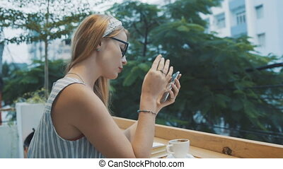 Woman using app on smartphone in tarrace of cafe. Young girl smiling and taking off her glasses.