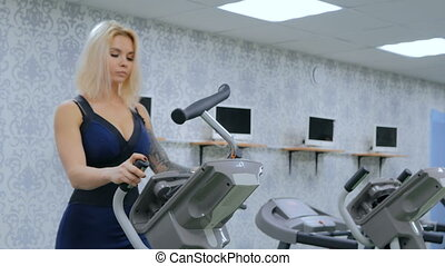 Athletic young woman working out on stepper machine at the...