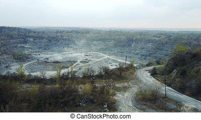 Flying over a stone quarry - The flight of a quadrocopter in...