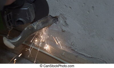 Plumber with angle grinder dismantling old cast iron...