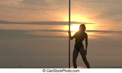 Pole dance fitness exercise on the beach at sunset