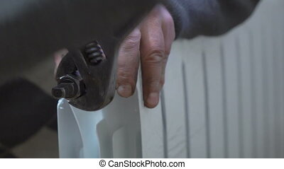 New hot water radiator installation. Closeup of a plumber...