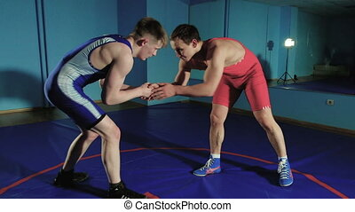 two wrestlers Greco-Roman wrestling on the blue background...