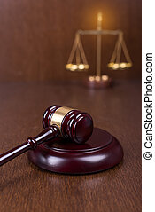 Wooden gavel with scales on wooden table, law concept