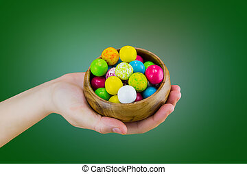 Bright candy chewing gum in a wooden bowl dish lies on the palm of hand on a green background macro