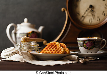 Viennese wafers on dark table with tea cup