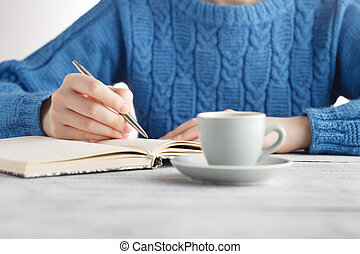 Woman write in notebook and drink coffee