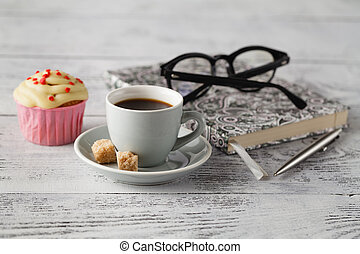 Cup of coffee and muffin on office table in begining of...