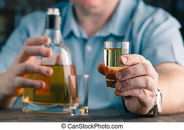 man offers whiskey. Elegant man keeps and holds a glass